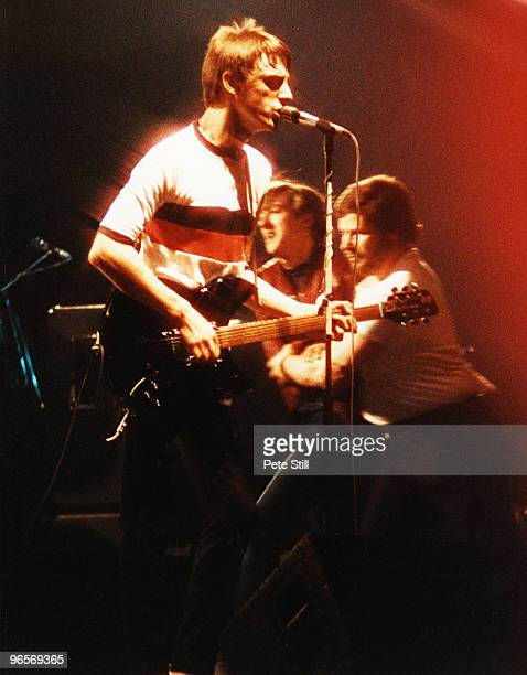 Paul Weller of The Jam performs at Wembley Arena while a member of the audience is escorted off the stage by security personel on December 3rd 1982...