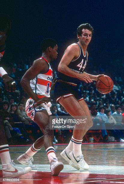 Paul Westphal of the New York Knicks backs in on Bryan Warrick of the Washington Bullets during an NBA basketball game circa 1982 at the Capital...
