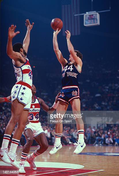 Paul Westphal of the New York Knicks shoots over Billy Ray Bates and Greg Ballard of the Washington Bullets during an NBA basketball game circa 1982...