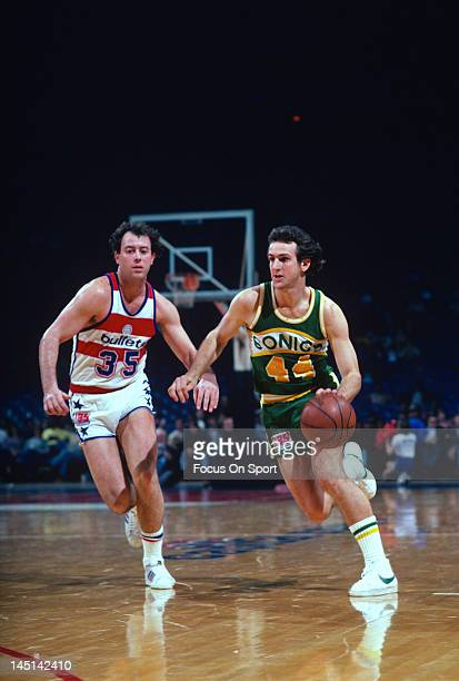 Paul Westphal of the Seattle Supersonics drives past Kevin Grevey of the Washington Bullets during an NBA basketball game circa 1981 at the Capital...