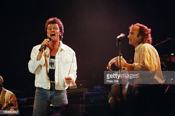 Paul Young and Phil Collins perform on stage at Wembley Arena for The Princes Trust on June 6th 1987 in London England Mark King of Level 42 is in...