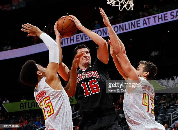 Paul Zipser of the Chicago Bulls drives between DeAndre Bembry and Kris Humphries of the Atlanta Hawks at Philips Arena on January 20 2017 in Atlanta...
