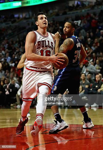 Paul Zipser of the Chicago Bulls drives past Devin Harris of the Dallas Mavericks at the United Center on January 17 2017 in Chicago Illinois The...