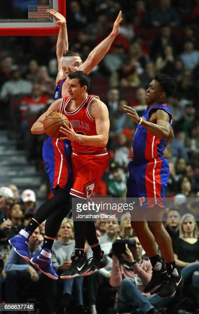 Paul Zipser of the Chicago Bulls leaps to pass between Aron Baynes and Stanley Johnson of the Detroit Pistons at the United Center on March 22 2017...