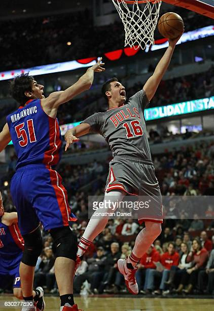 Paul Zipser of the Chicago Bulls puts up a shot past Boban Marjanovic of the Detroit Pistons at the United Center on December 19 2016 in Chicago...