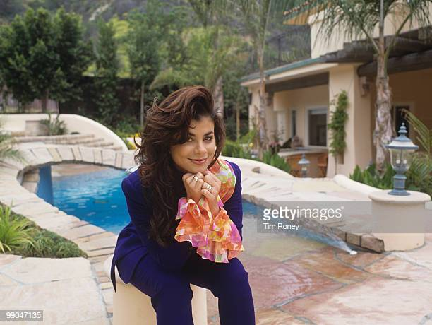 Paula Abdul singer and choreographer sitting by a swimming pool circa 1990