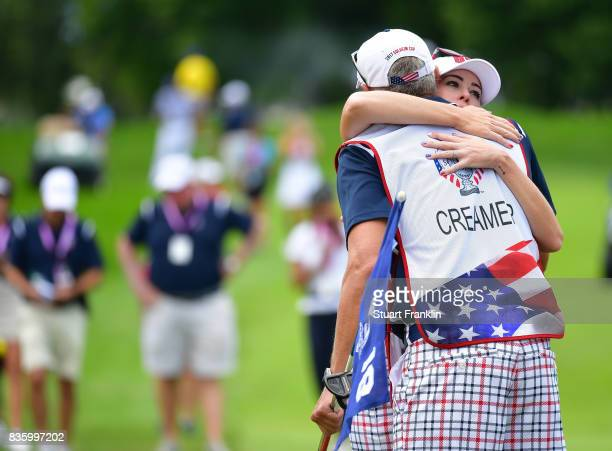 Paula Creamer of Team USA celebrates with her caddie on the 18th hole during the final day singles matches of The Solheim Cup at Des Moines Golf and...