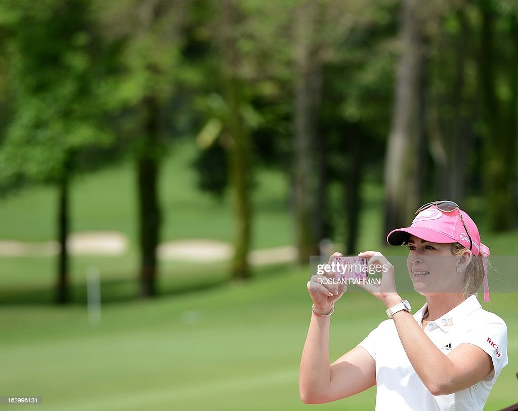Paula Creamer of the US takes a photo with her smartphone during the prize presentation at the HSBC Women's Champions LPGA golf tournament at the Serapong Course in Singapore on March 3, 2013. The 1.4 million USD tournament takes place from February 28 to March 3. AFP PHOTO / ROSLAN RAHMAN