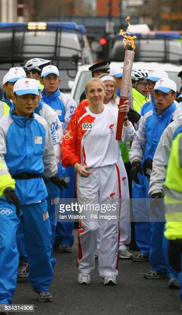 Paula Radcliffe carries the Olympic torch during its relay journey across London on its way to the lighting of the Olympic cauldron at the O2 Arena...