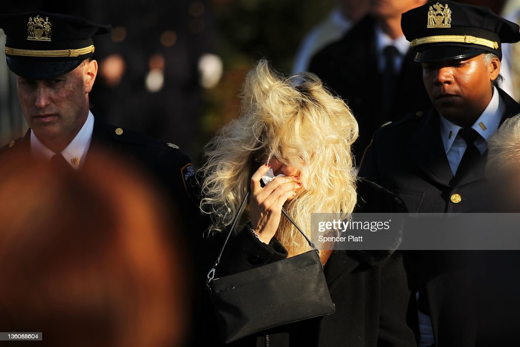 Paulette Figoski the exwife of murdered NYPD officer Peter Figoski grieves as his casket is brought out during the funeral at St Joseph's Church on...