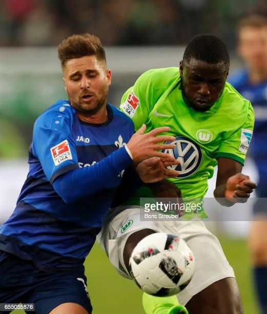 PaulGeorges Ntep of VfL Wolfsburg is challenged by Markus Steinhoefer of SV Darmstadt 98 during the Bundesliga match between VfL Wolfsburg and SV...