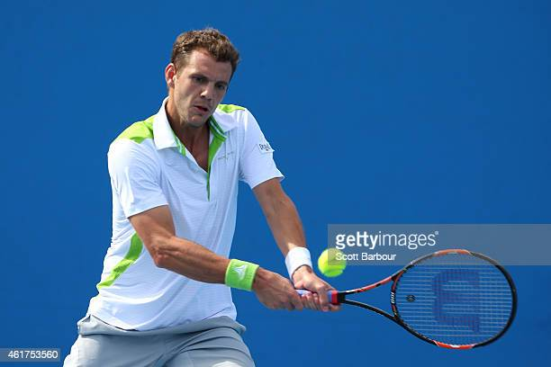 PaulHenri Mathieu of France plays a backhand in his first round match against Philipp Kohlschreiber of Germany during day one of the 2015 Australian...