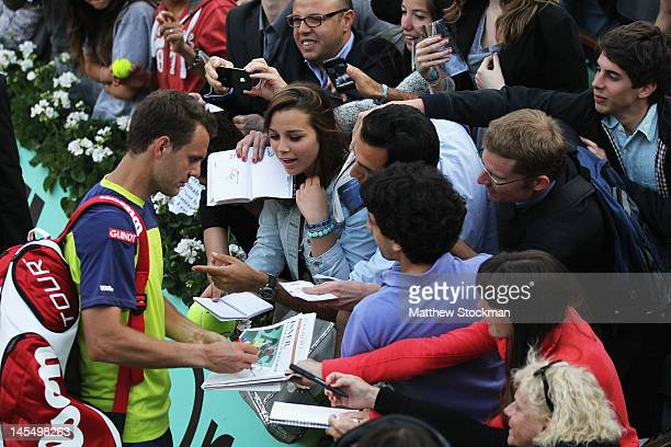 PaulHenri Mathieu of France signs autographs for fans after victory in his men's singles second round match against John Isner of USA during day 5 of...