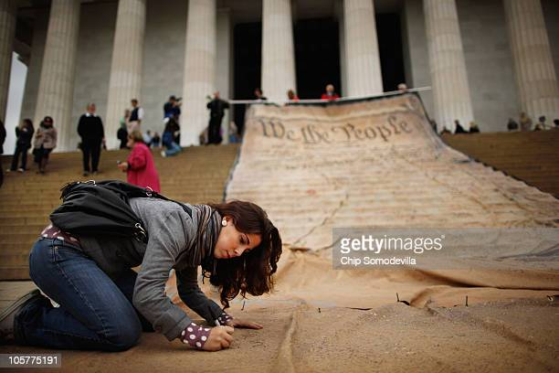 Paulina Perez signs a giant banner printed with the Preamble to the United States Constitution during a demonstration against the Supreme Court's...