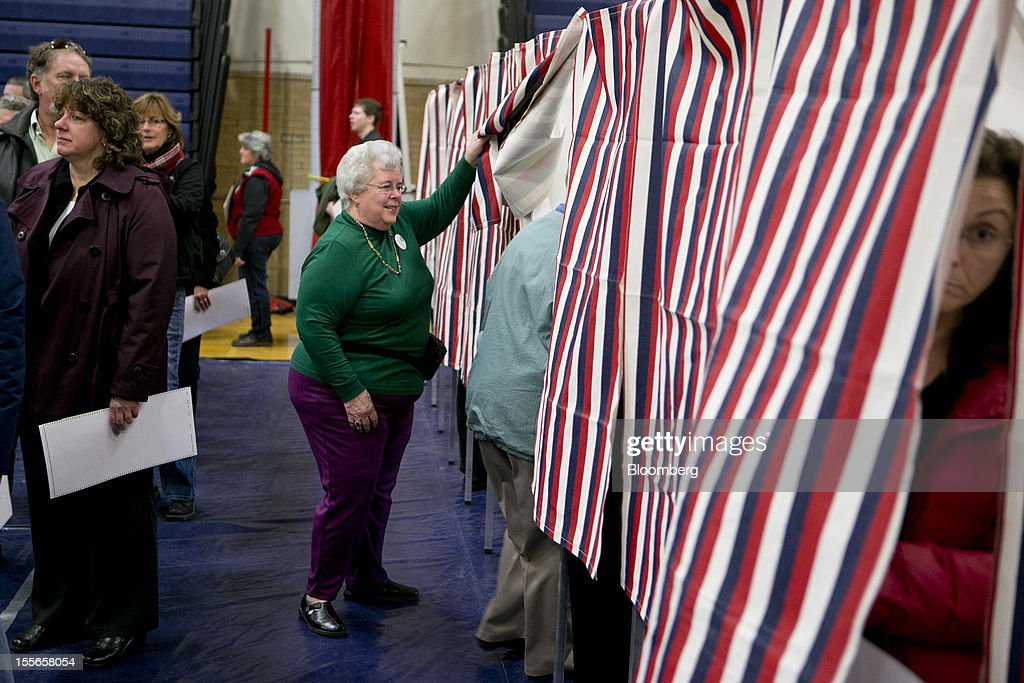 Pauline DesRochers helps a voter into a booth at a polling station in Manchester, New Hampshire, U.S., on Tuesday, Nov. 6, 2012. U.S. President Obama is seeking to overcome the drag of high unemployment and economic weakness that has frustrated predecessors' re-election bids, while his Republican rival Mitt Romney reaches for an upset to propel him beyond his party's standing and swamp an electoral map stacked against him on the final day of the presidential race. Photographer: Andrew Harrer/Bloomberg via Getty Images