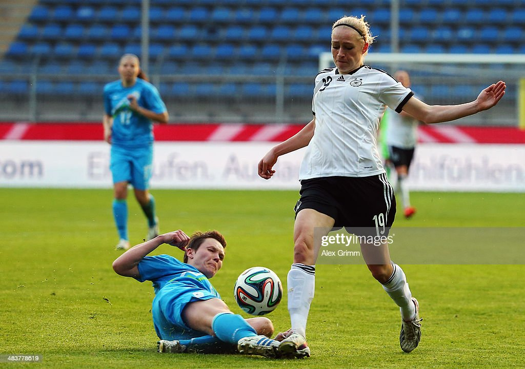 Pauline-Marie Bremer of Germany is challenged by Lucija Grad of Slovenia during the FIFA Women's World Cup 2015 qualifying match between Germany and Slovenia at Carl-Benz-Stadion on April 10, 2014 in Mannheim, Germany.