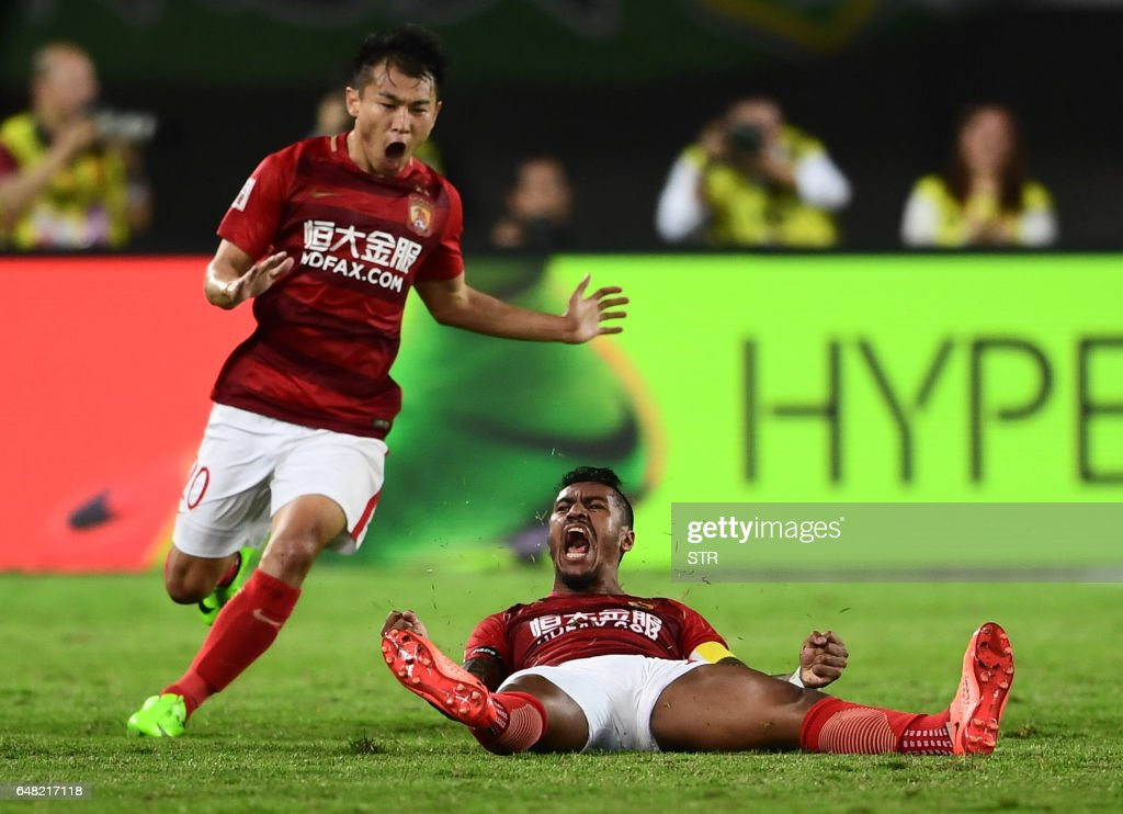 Paulinho (R) and Yu Hanchao (L) of Guangzhou Evergrande celebrate at the end of their Chinese Super League football match against Beijing Guoan in Guangzhou, in China's Guangdong province on March 5, 2017. /