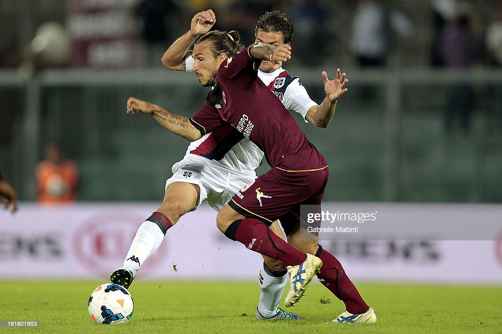 Paulinho of As Livorno Calcio battles for the ball with <a gi-track='captionPersonalityLinkClicked' href=/galleries/search?phrase=Daniele+Dessena&family=editorial&specificpeople=728068 ng-click='$event.stopPropagation()'>Daniele Dessena</a> of Cagliari Calcio during the Serie A match between AS Livorno and Cagliari Calcio at Stadio Armando Picchi on September 25, 2013 in Livorno, Italy.