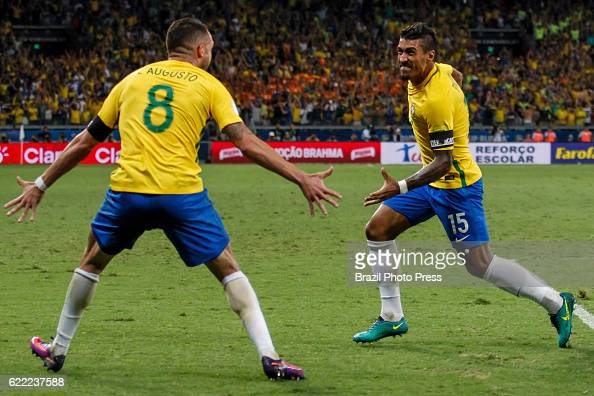 Paulinho of Brazil celebrates with teammate Renato Augusto after scoring the third goal of his team during a match between Argentina and Brazil as...