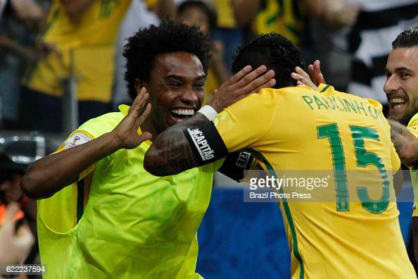 Paulinho of Brazil celebrates with teammate Willian after scoring the third goal of his team during a match between Argentina and Brazil as part of...