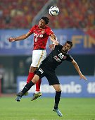 Paulinho of China's Guangzhou Evergrande competes for the ball with Majed Hassan of the UAE's Al Ahli during the AFC Champions League football final...