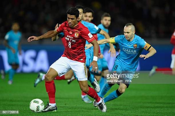 Paulinho of Guangzhou Evergrande FC is challenged by Andres Iniesta of Barcelona during the FIFA Club World Cup Japan 2015 Semi Final match between...