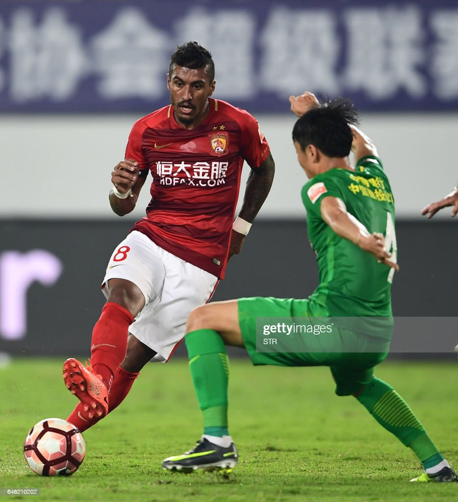 Paulinho of Guangzhou Evergrande L fights for the ball with Li