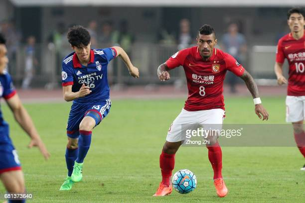 Paulinho of Guangzhou Evergrande in action against Lee Jong Sung of Suwon Samsung Bluewings during the AFC Champions League Group G match between...