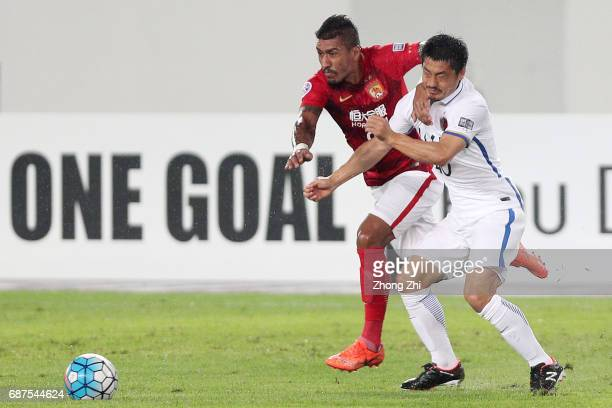 Paulinho of Guangzhou Evergrande in action against Ogasawara Mitsuo of Kashima Antlers during the AFC Champions League match between Guangzhou...