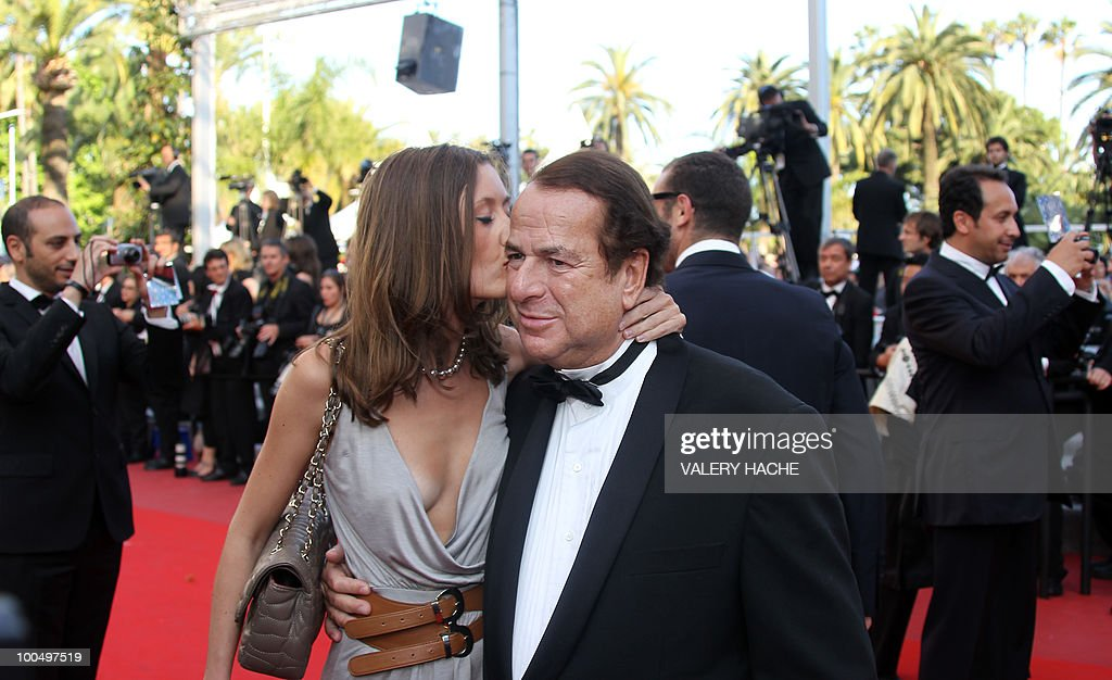 Paul-Loup Sulitzer is kissed by companion finance consultant Annabelle Rahal as they arrive for the screening of 'Utomlyonnye Solntsem 2: Predstoyanie' (The Exodus - Burnt By The Sun 2) presented in competition at the 63rd Cannes Film Festival on May 22, 2010 in Cannes.