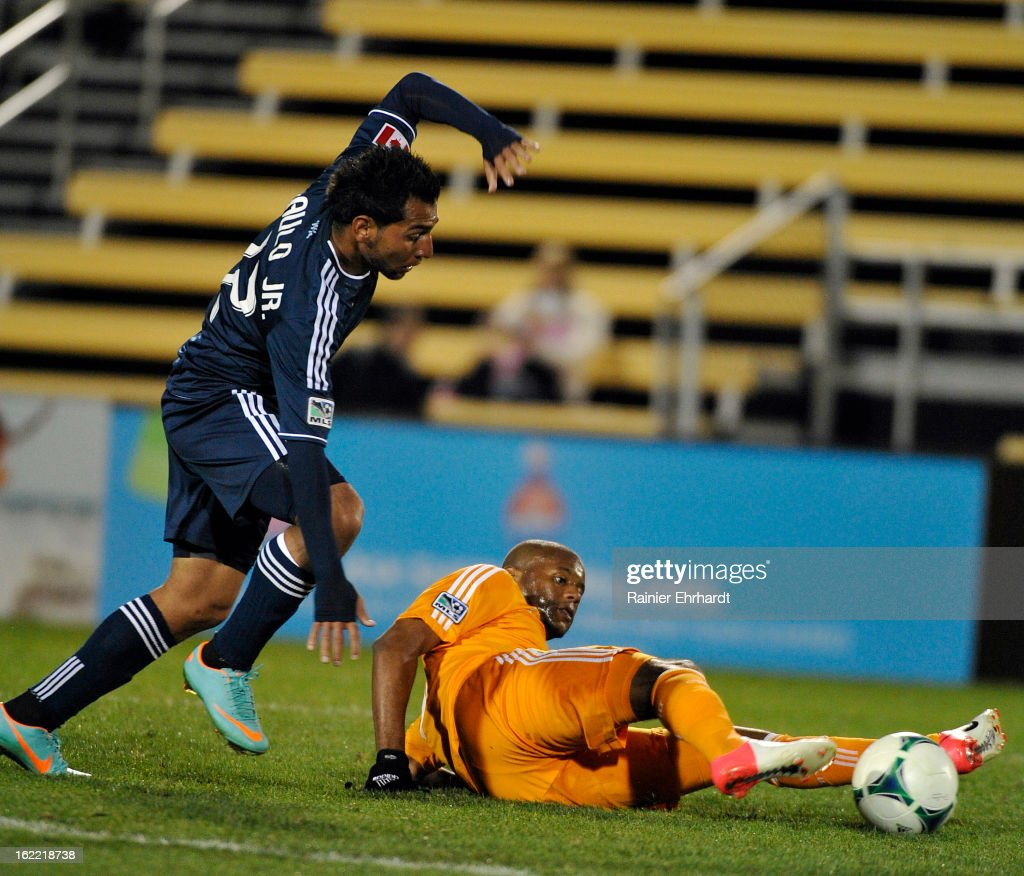 Paulo Araujo Jr. #22 of the Vancouver Whitecaps FC and Luiz Camargo #17 of the Houston Dynamo battle for the ball during the second half of a game at Blackbaud Stadium on February 20, 2013 in Charleston, North Carolina.