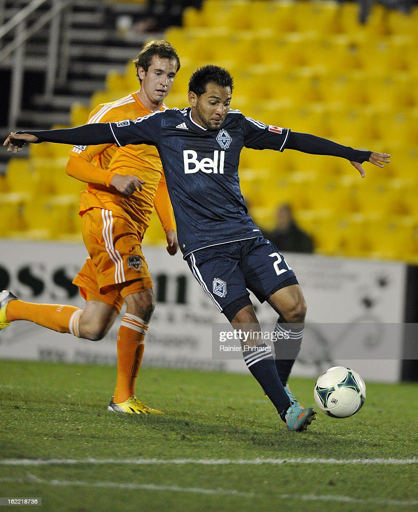 Paulo Araujo Jr. #22 of the Vancouver Whitecaps FC runs with the ball as Brian Ownby #22 of the Houston Dynamo defends during the second half of a game at Blackbaud Stadium on February 20, 2013 in Charleston, North Carolina.