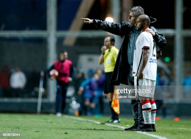 Paulo Autuori coach of Atletico Paranaense gives instructions to Jonathan during a group stage match between San Lorenzo and Atletico Paranaense as...