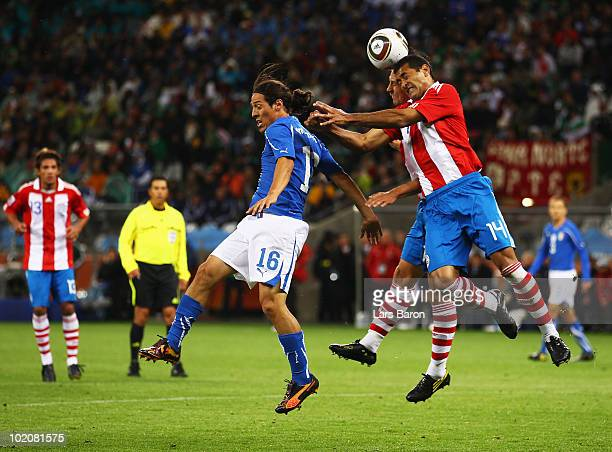 Paulo Da Silva of Paraguay jumps for a ball with Mauro Camoranesi of Italy during the 2010 FIFA World Cup South Africa Group F match between Italy...