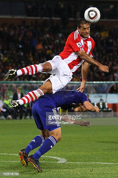 Paulo Da Silva of Paraguay jumps for a high ball above Makoto Hasebe of Japan during the 2010 FIFA World Cup South Africa Round of Sixteen match...