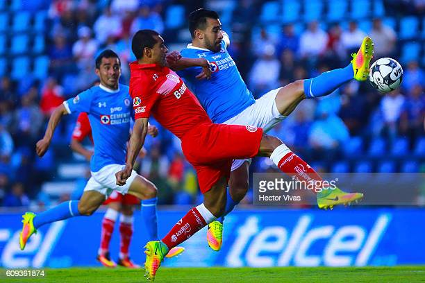 Paulo Da Silva of Toluca struggles for the ball with Ariel Rojas of Cruz Azul during the 10th round match between Cruz Azul and Toluca as part of the...