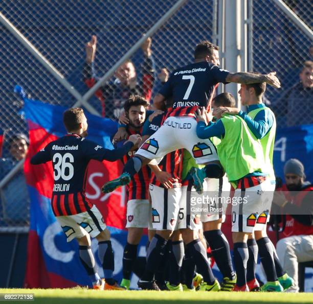 Paulo Diaz of San Lorenzo celebrates with teammates Franco Mussis and Bautista Merlini after scoring the second goal of his team during a match...