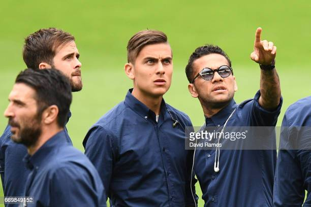 Paulo Dybala and Dani Alves of Juventus walk on the pitch prior to the Juventus press conference at the Camp Nou on April 18 2017 in Barcelona Spain