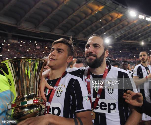 Paulo Dybala and Gonzalo Higuain of Juventus FC celebrates with the trophy after winning the TIM Cup Final match against SS Lazio and Juventus FC at...