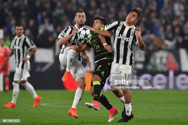 Paulo Dybala and Miralem Pjanic of Juventus clashe with Marcos Acuna of Sporting during the UEFA Champions League group D match between Juventus and...