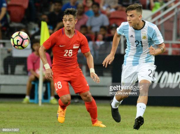 Paulo Dybala of Argentina competes for the ball with Hafiz Sujad of Singapore  of Singapore during their international friendly football match at the...