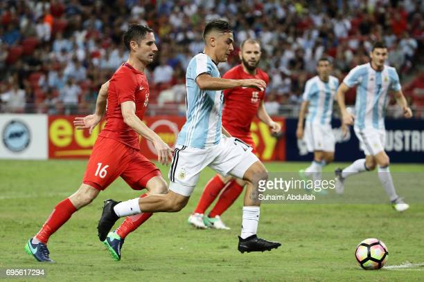 Paulo Dybala of Argentina dribbles past Daniel Bennett of Singapore during the International Test match between Argentina and Singapore at National...