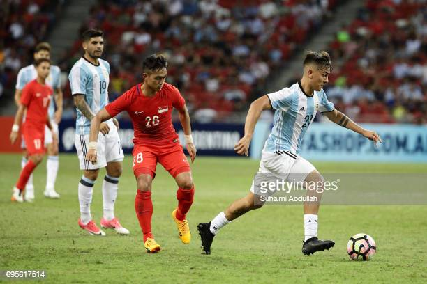 Paulo Dybala of Argentina dribbles past Hafiz Sujad of Singapore during the International Test match between Argentina and Singapore at National...