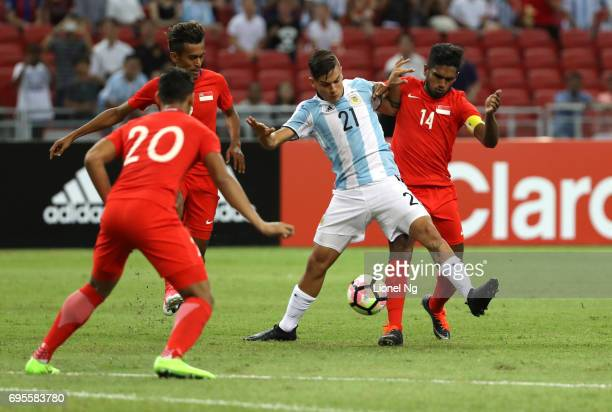 Paulo Dybala of Argentina is tackled by Hariss Harun of Singapore during the international friendly match between Argentina and Singapore at National...