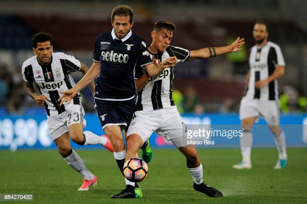Paulo Dybala of FC Juventus compete for the ball with Senad Lulic of SS Lazio during the TIM Cup Final match between SS Lazio and Juventus FC at...