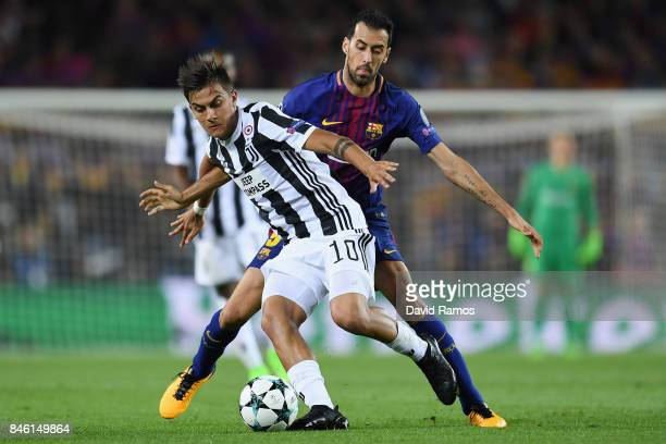Paulo Dybala of Juventus and Sergio Busquets of Barcelona battle for possession during the UEFA Champions League Group D match between FC Barcelona...