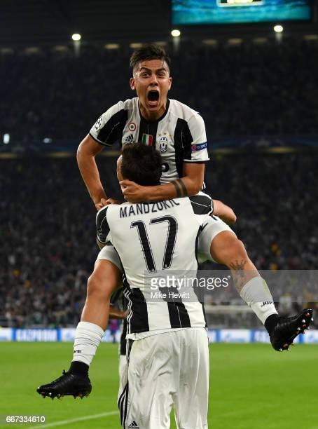 Paulo Dybala of Juventus celebrates with Mario Mandzukic after scoring a goal during the UEFA Champions League Quarter Final first leg match between...