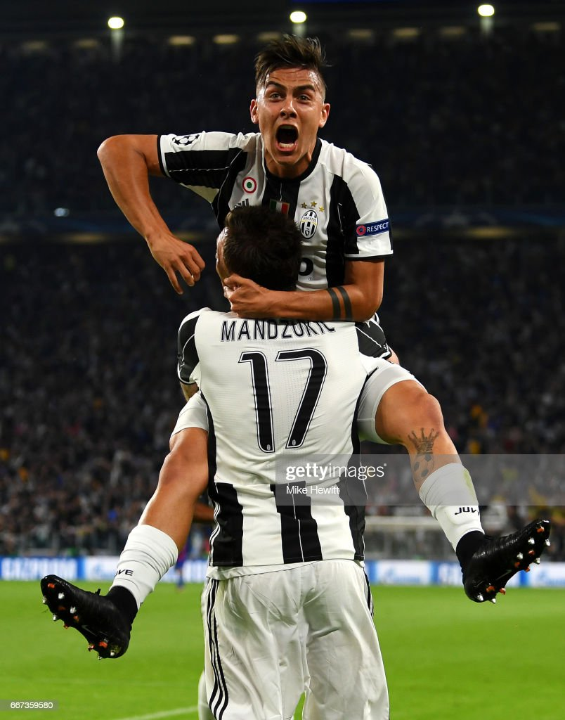 Paulo Dybala of Juventus celebrates with Mario Mandzukic after scoring his team's second goal during the UEFA Champions League Quarter Final first leg match between Juventus and FC Barcelona at Juventus Stadium on April 11, 2017 in Turin, Italy.