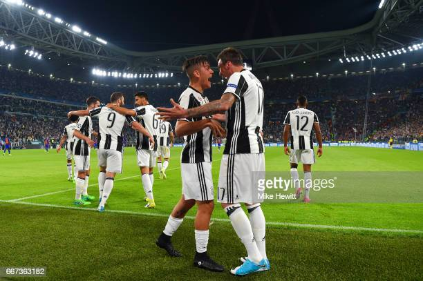 Paulo Dybala of Juventus celebrates with Mario Mandzukic after scoring his team's second goal during the UEFA Champions League Quarter Final first...