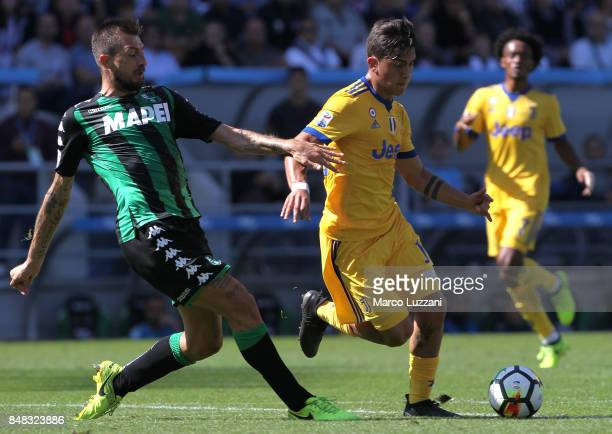 Paulo Dybala of Juventus competes for the ball with Francesco Acerbi of US Sassuolo Calcio during the Serie A match between US Sassuolo and Juventus...